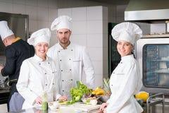 Um grupo de cozinheiros chefe novos que prepairing a refeição no restaurante luxuoso imagem de stock royalty free