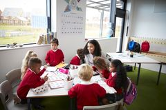 Um grupo de crianças da escola infantil que sentam-se em uma tabela em uma sala de aula com seu professor fêmea fotografia de stock royalty free