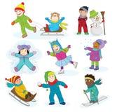 Um grupo de crianças felizes que jogam na neve e que têm o divertimento durante as férias do inverno Fotografia de Stock Royalty Free