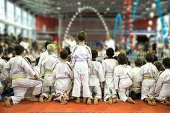 Um grupo de crianças no quimono Olhe um desempenho da demonstração de mestres do karaté foto de stock