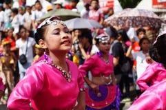 Um grupo de dançarinos fêmeas do carnaval em vários trajes dança no prazer ao longo da estrada Imagem de Stock Royalty Free