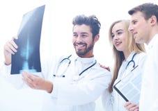 Um grupo de doutores que examinam um raio X no hospital Imagem de Stock