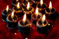 Um grupo de doze velas pretas iluminou o assento em uma grande associação de sangue Fundo assustador perfeito para Dia das Bruxas foto de stock