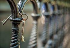 Um grupo de duas chaves velhas da porta do vintage do metal que penduram em uma cerca do ferro fundido da carcaça artística em um fotos de stock
