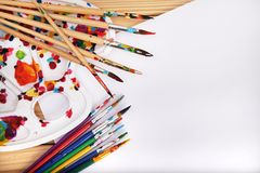 Um grupo de escovas da arte, de uma armação e do Livro Branco em uma tabela de madeira na oficina do ` s do artista Imagens de Stock Royalty Free