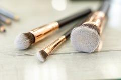 Um grupo de escovas para a composição encontra-se na tabela no salão de beleza fotos de stock royalty free