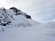 Um grupo de esquiadores backcountry que caminham ao longo de uma cara norte íngreme e o pico alpino alto em sua maneira à parte s Fotografia de Stock Royalty Free