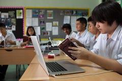 Um grupo de estudantes em uma sala de aula que trabalha junto em um exercício Imagem de Stock