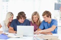 Um grupo de estudantes usa um portátil para responder a suas perguntas Imagens de Stock