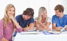 Um grupo de estudo que trabalha duramente como uma menina sorri   Fotografia de Stock Royalty Free