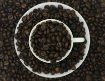 Um grupo de feijões de café no copo e nos pires com os feijões no fundo Imagem de Stock