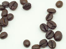 Um grupo de feijões de café finos está em um fundo branco Foto de Stock