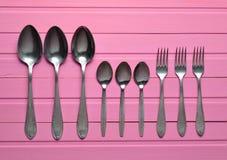 Um grupo de forquilhas, colheres em uma tabela de madeira cor-de-rosa cutlery Vista superior Fotos de Stock