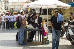 Um grupo de homens judaicos que conversam junto sob um parasol da máscara do sol no mercado de rua de Mahane Yehuda no Jerusalém  imagens de stock