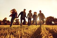 Um grupo de jovens que correm através da grama no parque no por do sol fotografia de stock