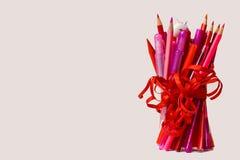 Um grupo de lápis apontados, de canetas com ponta de feltro em vermelho e em cor-de-rosa, e de uma pena na forma de um unicórnio, fotografia de stock royalty free