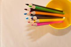 Um grupo de lápis coloridos em um vidro Fundo bege fotos de stock royalty free