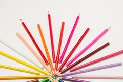 Um grupo de lápis dobrou-se em cores do arco-íris em um círculo em um whi Imagem de Stock