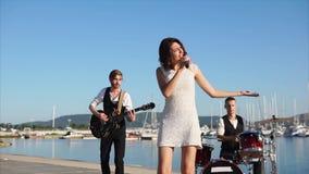 Um grupo de músicos da rua que executam no evento de gala perto do mar no dia vídeos de arquivo