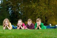 Um grupo de miúdos que coloc na grama Fotos de Stock