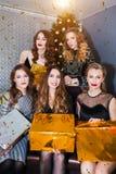 Um grupo de mulheres bonitas novas comemora o ano novo, Natal Confetes, caixa de presente, emoções positivas fotos de stock