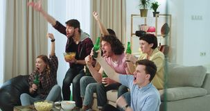 Um grupo de multi étnico dos amigos muito carismáticos olhando um fósforo de futebol junto feliz e excitado apoiam o seu vídeos de arquivo