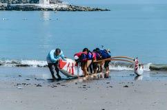 Um grupo de paddlers das crianças que puxam um barco para a costa um o dia de verão foto de stock