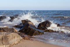 Um grupo de pedras na costa e espirra das ondas Imagens de Stock