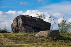 Um grupo de pedras que encontram-se na grama verde da mola em Murmansk em um dia claro, ensolarado Fotografia de Stock