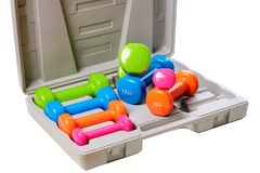 Um grupo de pesos isolados coloridos para esportes em um fundo branco é empilhado em uma caixa cinzenta Fotografia de Stock Royalty Free