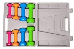 Um grupo de pesos isolados coloridos para esportes em um fundo branco é empilhado em uma caixa cinzenta de cima de Fotografia de Stock