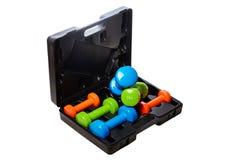 Um grupo de pesos isolados coloridos para esportes em um fundo branco é empilhado em uma caixa preta Imagem de Stock