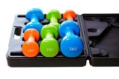 Um grupo de pesos isolados coloridos para esportes em um fundo branco é empilhado em uma caixa preta Fotografia de Stock Royalty Free