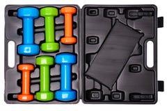 Um grupo de pesos isolados coloridos para esportes em um fundo branco é empilhado em uma caixa preta de cima de Foto de Stock