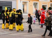 Um grupo de pessoas em trajes do carnaval fala na frente de uma construção Foto de Stock