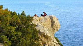 Um grupo de pessoas estabeleceu-se para baixo para descansar em uma rocha acima do mar fotos de stock royalty free