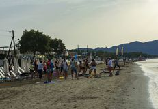 Um grupo de pessoas executa exercícios físicos na praia Fotografia de Stock