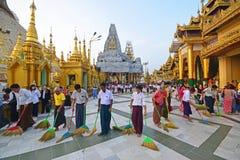 Um grupo de pessoas que trabalha junto em equipe para varrer o assoalho no pagode de Shwedagon fotografia de stock