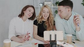 Um grupo de proprietários empresariais criativos lança um webinar em linha Mulher loura nova bonita, homem considerável nos vidro video estoque