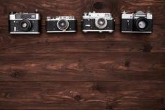 Um grupo de quatro câmeras antiquados com um espaço da cópia Foto de Stock Royalty Free