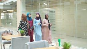 Um grupo de quatro meninas multi-?tnicos mu?ulmanas novas que conversam e que andam junto no centro de neg?cio filme