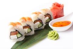 Um grupo de rolos de sushi com camarão e o queijo creme apresentados em uma banana folheiam com um molho picante Imagens de Stock Royalty Free