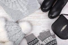 Um grupo de roupa elegante do ` s das mulheres do inverno Camiseta de lãs, sapatas, bolsa, chapéu forrado a pele e luvas no fundo Foto de Stock