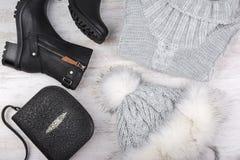 Um grupo de roupa elegante do ` s das mulheres do inverno Camiseta de lãs, sapatas, bolsa e chapéu forrado a pele no fundo de mad Imagem de Stock