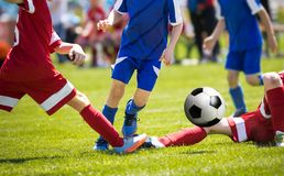 Um grupo de runnng novo dos jogadores de futebol a bola Brocas do jogador de futebol e tentativa pingando do equipamento Imagens de Stock