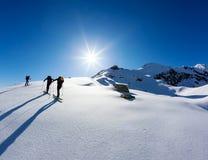 Um grupo de skialpers trabalha junto para alcançar a cimeira da montanha fotos de stock royalty free