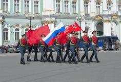 Um grupo de soldados com a bandeira da vitória e a bandeira do russo no março solene Ensaio de parada em honra da vitória D Fotos de Stock
