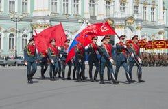 Um grupo de soldados com a bandeira da vitória e a bandeira do russo no março solene Ensaio de parada em honra da vitória D Imagens de Stock