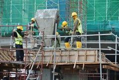 Um grupo de trabalhadores da construção que derramam o concreto molhado Imagem de Stock Royalty Free