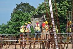 Um grupo de trabalhadores da construção que derramam o concreto molhado Foto de Stock Royalty Free